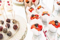 Suikergoedbar met heel wat desserts, schuimgebakje, cupcake, fruit en zoete cakes Zoete lijst voor verjaardag of huwelijk Stock Afbeeldingen
