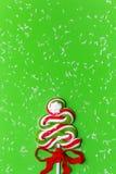 Suikergoedkerstboom en sneeuwval op groene achtergrond royalty-vrije stock foto's