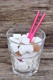 Suikerkubussen in glas met roze stro op rustieke lijst Royalty-vrije Stock Afbeelding