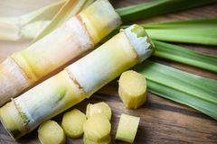 suikerriet en groen het suikerrietstuk van de bladbesnoeiing op houten lijstachtergrond royalty-vrije stock foto's