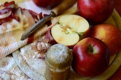 Suikerschudbeker, appelen en schilmes op houten hakbord Stock Fotografie