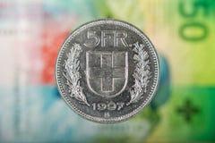 5 Suisses Franc Coin avec 50 Suisses Franc Bill comme fond Images stock