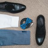 Suit, blue bow tie, leather black shoes and belt. Grooms wedding morning. Close up of modern man accessories. Look from above Stock Photos