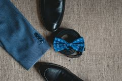 Suit, blue bow tie, leather black shoes and belt. Grooms wedding morning. Close up of modern man accessories. Look from above Stock Photo