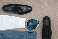Suit, blue bow tie, leather black shoes and belt. Grooms wedding morning. Close up of modern man accessories. Look from above Royalty Free Stock Image