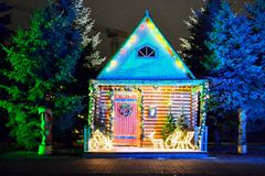 Suit and cozy house near forest decorated for the winter holidays. Colored lights around the front of the building. New year and stock photos