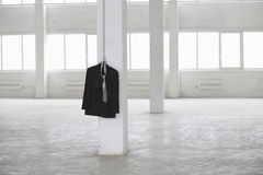 Suit Jacket Hanging On Pillar In Warehouse Royalty Free Stock Images