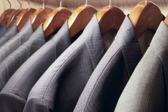 Suit jackets. Row of men's suit jackets hanging in closet stock images
