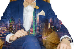 Suit man with big city double exposure. Man in blue suit with coffee cream bowtie color, flower brooch, and dot pattern pocket square sitting on cozy sofa stock images