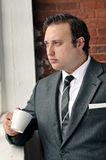 Suit man drinks coffee and thinks Royalty Free Stock Photo