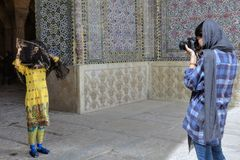 Suit photo session near entrance to the mosque, Shiraz, Iran. Fars Province, Shiraz, Iran - 19 april, 2017: The girl photographer photographs a model in a Stock Image