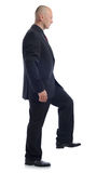 Suit step up. Side view of man in suit stepping up isolated on white Stock Photography