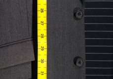 Suit and Tape Measure. Pin-Striped Business Suit with Yellow Tape Measure Royalty Free Stock Images