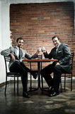 Suit wearing men make a deal. Business deal in a cafe, agreed with cappuccinos Royalty Free Stock Photos