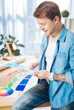 Experienced designer holding color palettes and smiling happily. Suitable colors. Enthusiastic young creative designer looking happy while sitting with different royalty free stock image