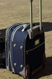 Suitcase. Asphalt worth suitcase luggage blue color with the lifted handle Royalty Free Stock Images