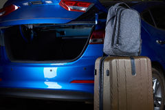 Suitcase and backpack next to open car trunk Stock Photos