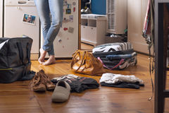 Suitcase and bags on the floor, young woman in jeans and with bare feet standing in the background Stock Photo