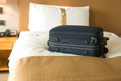 Suitcase on bed Stock Photography
