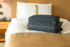 Suitcase on bed Stock Photo