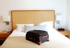 Suitcase on the bed inside a hotel room Royalty Free Stock Images