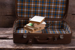 Suitcase with books on the old boards. Royalty Free Stock Photo
