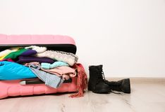 Suitcase with clothes and boots on floor against wall, space for text. Winter vacation. Suitcase with clothes and boots on floor against white wall, space for stock images