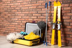 Suitcase with clothes, camera and skis on floor against brick wall, space for text. Winter vacation stock photo
