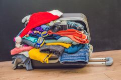A suitcase with clothes and a Christmas hat. Journey to Christma. S Royalty Free Stock Photo