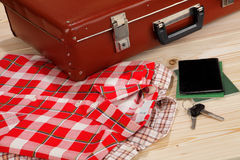Suitcase and clothes on wooden background Royalty Free Stock Image