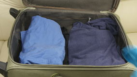 Suitcase with clothing. On bed in room stock video footage