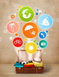Suitcase with colorful summer icons and symbols. On grungy background Stock Images