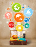 Suitcase with colorful summer icons and symbols. On grungy background Stock Image