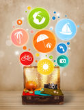 Suitcase with colorful summer icons and symbols. On grungy background Stock Photo