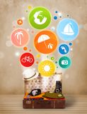 Suitcase with colorful summer icons and symbols. On grungy background Royalty Free Stock Photos