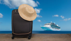 Suitcase and cruise ship. Suitcase with summer hat on top. Cruise ship in the background Stock Photos