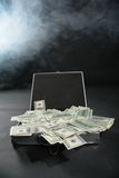 Suitcase with dollars against smoke Stock Photos