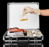 Suitcase with dollars,  pistol and  hand holding  drugs isolated. Royalty Free Stock Photo
