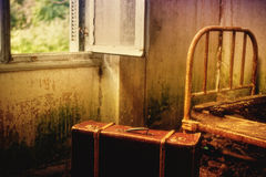 Suitcase in an empty room. Suitcase in an empty abandoned dirty room royalty free stock image