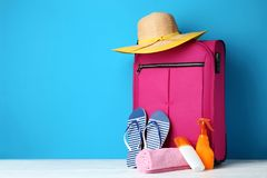 Suitcase with flip-flops, hat and sunscreen. Pink suitcase with flip-flops, hat and sunscreen bottles on wooden table royalty free stock images
