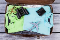 Suitcase with folded clothes and accessories. Binoculars, wallet and toy airplane on packed clothes in suitcase Royalty Free Stock Photo