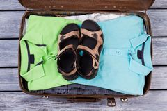 Suitcase with folded male clothes and pair of sandals. Open old suitcase on wooden table, ready for travel and vacation Royalty Free Stock Images