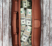 Suitcase full of dollars on a wooden background. Royalty Free Stock Photo