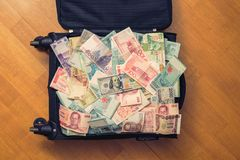 Suitcase full money of south-east Asia and American hundred dollar bill. Currency of Hong Kong, Indonesia, Malaysia, Thai, Singapo Royalty Free Stock Photos