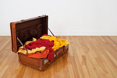 Suitcase full of orange and yellow clothing Stock Image