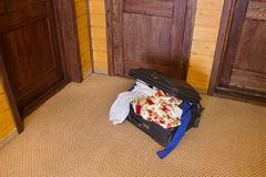 Suitcase full of things at the door Stock Image