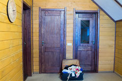 Suitcase full of things at the door Royalty Free Stock Images
