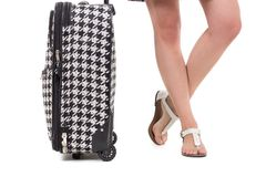 Suitcase and girl's feet wearing sandals Royalty Free Stock Photography