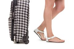 Suitcase and girl's feet wearing sandals Royalty Free Stock Photos