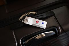 Suitcase with Japan Airlines Corporation JAL luggage tag royalty free stock photography